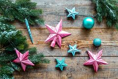 Decorate the christmas tree. Pink and blue stars and balls near pine branches on wooden background top view Stock Image