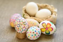 Decorate and Colored drawings on eggs. Painted Souvenirs Easter eggs in a wicker basket on a wooden table Colored drawings royalty free stock images