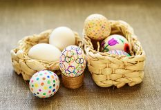 Decorate eggs for Easter. Colored drawings. Easter eggs in a wicker basket on the tablecloth of burlap stock photo