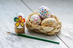Decorate eggs for Easter. Colored drawings on Easter eggs. Easter eggs in a wicker basket on a wooden table royalty free stock image