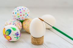 Decorate eggs for Easter. Hand painted Easter eggs.Colored drawings. Easter eggs in a wicker basket on a wooden table royalty free stock image