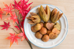 Decorate fruit in a plate. Decorate sapodillas in a plate on the table near maple leaf Stock Photo