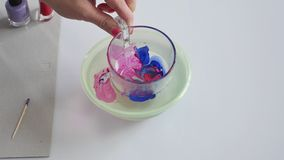 Decorate a glass with nail polish, art craft diy. Decorate a glass using handmade method, nail polish and water, art craft diy, do it yourself stock video footage