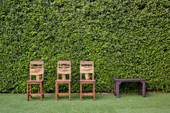 Decorate three wooden chairs and coffee table against the green Royalty Free Stock Photography