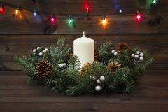Decorated Advent wreath with a white candle on a wooden background with a shining multicolored garland Royalty Free Stock Photo