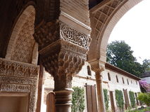 Decorated arches and columns in the Alhambra. Arches and columns carved and decorated inside the Nasrid Palace (Palacio Nazaries), part of the complex of the Royalty Free Stock Photography