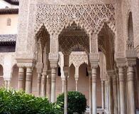 Decorated arches and columns in the Alhambra. Arches and columns carved and decorated inside the Nasrid Palace (Palacio Nazaries), part of the complex of the Royalty Free Stock Photos