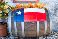 Decorated Barrel in Front of a Texas Building. Weathered wooden barrel with a bright Texas flag painted on the front royalty free stock image