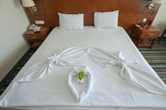 Decorated bed with towels and heart-shaped covers stock photos