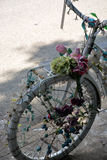 Decorated bicycle. Front wheel and handlebars of a bike decorated with lights and artificial flowers Royalty Free Stock Image