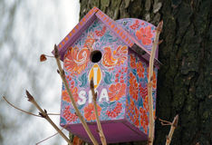 Decorated birdhouse on the trunk Stock Images