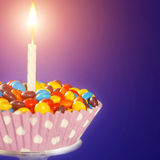 Decorated Birthday cupcake with one lit candle and Royalty Free Stock Photo