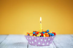 Decorated Birthday cupcake with one lit candle and Royalty Free Stock Image