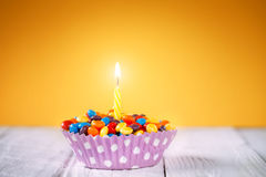 Decorated Birthday cupcake with one lit candle and Royalty Free Stock Photography
