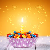 Decorated Birthday cupcake with one lit candle and Royalty Free Stock Images
