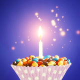Decorated Birthday cupcake with one lit candle and colorful candies on yellow background. Holidays greeting card Royalty Free Stock Photo