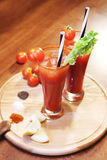 Decorated  bloody Mary. Decorated bloody Mary with celery and tomato. Alcoholic cocktail, drinks on a wooden board. Called Bloody Mary. Good cocktail booze with Stock Photography