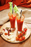 Decorated  bloody Mary. Decorated bloody Mary with celery and tomato. Alcoholic cocktail, drinks on a wooden board. Called Bloody Mary. Good cocktail booze with Stock Photos
