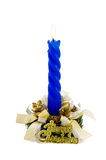 Decorated blue Christmas candle on white. A blue Christmas candle decorated with candlestick and ribbons Stock Images