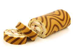 Decorated blueberry cream pastry roll. And some cut pieces on a white background stock image