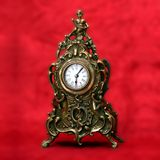 Decorated bronze clock. Antique decorated bronze clock on a red velvet background Royalty Free Stock Photography