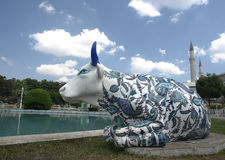 Decorated bull statue. A closeup of a statue of a bull, decorated with intricate blue designs painted on it. Statue has been placed next to a pool Stock Photo