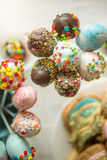 Decorated cake pops in cups on wooden table Stock Photography