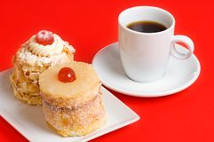 Decorated cakes and coffee. Two decorated cakes and a coffee cup with red background Royalty Free Stock Photos