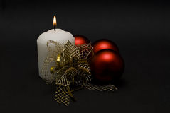 Decorated candle and three balls. Stock Photography