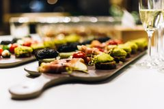 Decorated catering banquet table. With different food snacks and wine. Shallow depth of field Stock Images