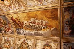 Decorated ceiling with frescos of a cart with horses in the museum Palazzo Te in Mantova, Italy Stock Image