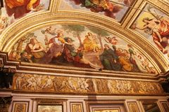 Decorated ceiling with frescos in the museum Palazzo Te in Mantova, Italy. Photo of decorated ceiling and walls with frescos of angels, saints and musicians in Royalty Free Stock Images