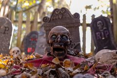 Decorated cemetery with tombstones, zombies and skeletal remains. stock photo