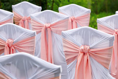 Decorated chairs for guests at  wedding in the garden. Royalty Free Stock Image