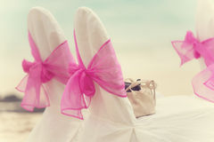Decorated chairs with wedding arrangement on the beach. Chairs decorated by pink ribbon for beach wedding. Creamy tonning Stock Photo