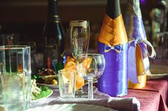 Decorated champagne bottles and wine glasses stand on a banquet served table. stock photos