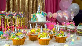 Decorated children`s birthday party with tasty cupcakes, colourful lollipops and unicorn cake. On a birthday table, against colorful background. Pink and white stock video footage