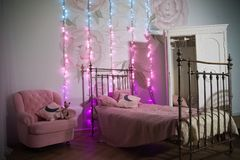 Decorated children`s room for Christmas. Bed, white wardrobe and chair, decorated for the New Year royalty free stock photography