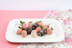 Decorated chocolate covered strawberries. On a white plate for Valentine`s Day treat Royalty Free Stock Photos