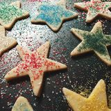 Decorated Christmas Cookies. Holiday cookies on a baking sheet waiting to be baked covered in sprinkle decorations Stock Image