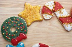 Decorated Christmas Cut Out Cookies on Natural Wood Grain. Highly decorated and colorful Christmas cut out cookies that are homemade and set on natural wood Royalty Free Stock Image