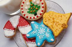 Decorated Christmas Cut Out Cookies on Plate With Glass. Highly decorated and colorful Christmas cut out cookies that are homemade and set on a clear plate, next Stock Photography