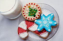 Decorated Christmas Cut Out Cookies on Plate With Glass. Highly decorated and colorful Christmas cut out cookies that are homemade and set on a clear plate, next Royalty Free Stock Image