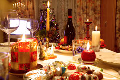 Decorated christmas dining table. With glasses and christmas tree in background Stock Images