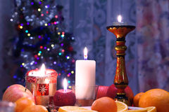 Decorated christmas dining table. With candles and christmas tree in background Royalty Free Stock Image