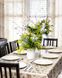Decorated Christmas dining table. Dining table decorated for Christmas with eight place settings and evergreen centerpiece Royalty Free Stock Photo