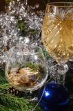 A decorated christmas dining table with champagne glasses and christmas tree in background royalty free stock photo