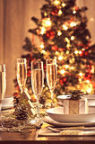Decorated christmas dining table. A decorated christmas dining table with champagne glasses and christmas tree in background Stock Photos