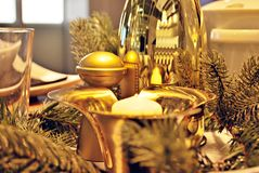 A decorated christmas dining table. Christmas table decorated with candles and christmas decorative objects. Festive christmas table place setting at home with Royalty Free Stock Photos