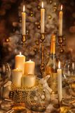 A decorated Christmas dining table. With sparkling wine, burning candles and Christmas tree in background Royalty Free Stock Photos